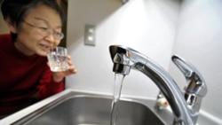 یک زن که لیوانی را از آب شیر در توکیو پر کرده است - ۳ فروردین ۱۳۹۰