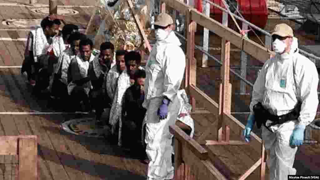 Sous le regard des militaires norvégiens, des migrants érythréens attendent de débarquer à Messine, Sicile, 6 octobre 2015 (Nicolas Pinault / VOA).
