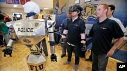 "FILE - Students control a ""Robocop"" during a demonstration at Florida International University in Miami."