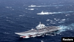 FILE - China's Liaoning aircraft carrier with accompanying fleet conducts a drill in an area of South China Sea, in this undated photo taken December 2016.
