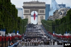 FILE - Troops wait near the Arc de Triomphe, in Paris, before taking part in the annual Bastille Day military parade on the Champs-Elysees avenue on July 14, 2016.