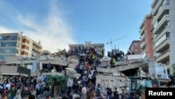 Procura de sobreviventes num prédio desabado, após um forteterramoto atingir o Mar Egeu, na sexta-feira