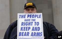 "FILE - John Doll, of Renton, Wash., holds a sign that reads ""The people have the right to keep and bear arms"" during a gun rights rally at the Capitol in Olympia, Wash."