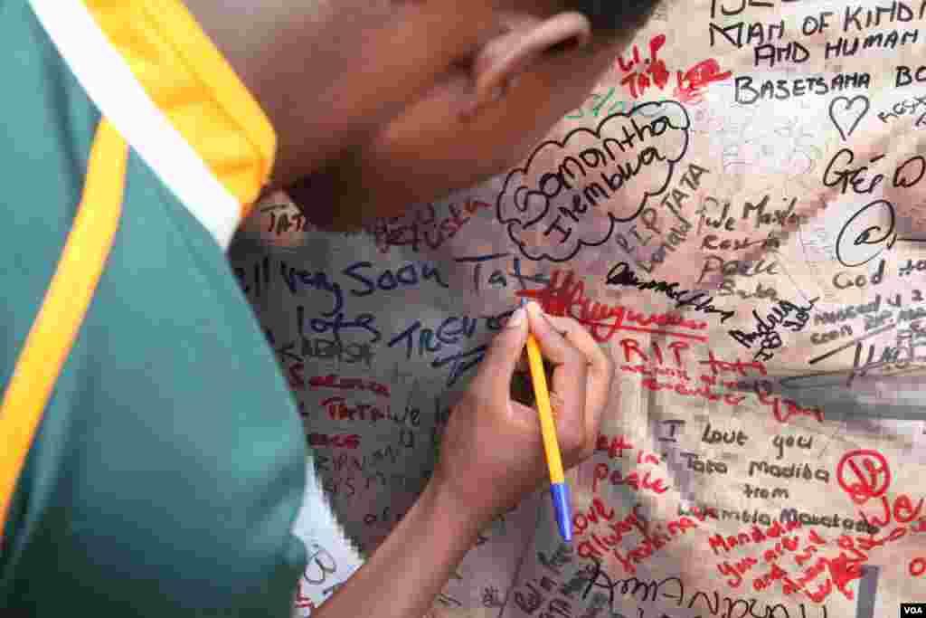 Um jovem escreve o seu nome num poster de Mandela à porta de sua casa em Soweto, África do Sul.(Hannah McNeish para VOA)