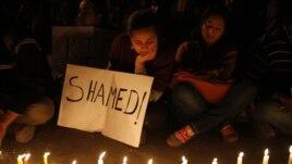 Warga menyalakan lilin tanda duka cita atas kematian korban pemerkosaan beramai-ramai di New Delhi (29/12). (AP/Saurabh Das)