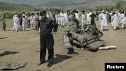A security official and residents inspect the site of a bomb attack in the Lower Dir tribal area in Pakistan September 16, 2012.