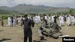 Seorang anggota pasukan keamanan dan penduduk setempat memeriksa lokasi ledakan bom pinggir jalan di daerah kesukuan Dir Bawah di Pakistan, dekat perbatasan Afghanistan (16/9).