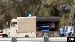 载着以色列前总理沙龙的灵柩的车队1月13日抵达墓地。