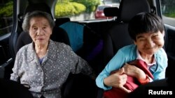 Congenital Minamata disease patient Shinobu Sakamoto, 61, and her mother, Fujie, sit in a car as they head for a hospital in Minamata, Kumamoto Prefecture, Japan, Sept. 14, 2017.