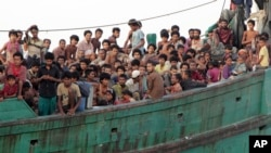 FILE - Migrants sit on their boat as they wait to be rescued by Acehnese fishermen on the sea off East Aceh, Indonesia, Wednesday, May 20, 2015. Hundreds of migrants stranded at sea for months were rescued and taken to Indonesia, officials said.