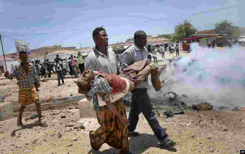 Men carry a seriously wounded man after an explosion in Mogadishu, Somalia, March 18, 2013.
