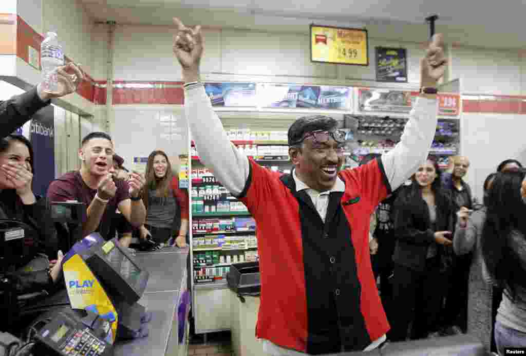 7-Eleven store clerk M. Faroqui celebrates after learning that his store sold a winning Powerball ticket, in Chino Hills, California, Jan. 13, 2016.