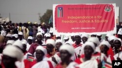 Southern Sudanese march and carry signs during a rehearsal for independence celebration, in the southern capital of Juba on Tuesday, July 5, 2011.