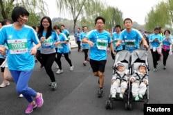 A man pushes a stroller carrying his 13-month-old twins as he runs the Hangzhou International Marathon, in Hangzhou, Zhejiang province, Nov. 2, 2014.