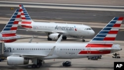 This July 17, 2019 photo shows American Airlines planes at Phoenix Sky Harbor International Airport in Phoenix.