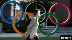 ٹوکیو میں ایک خاتون کرونا وائرس سے بچنے کے لیے چہرے پر ماسک لگائے اولمپکس میوزیم کے سامنے سے گزر رہی ہے۔ 13 مارچ 2020