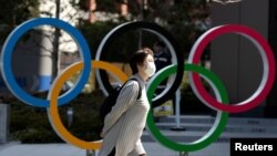 Seorang perempuan menggunakan masker pelindung berjalan melintas lambang Olimpiade, di depan Japan Olympics Museum di Tokyo, Jepang, di tengah wabah virus corona, 13 Maret 2020. (Foto: Reuters)