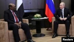Russian President Vladimir Putin talks with Sudan's President Omar al-Bashir during their meeting in the Black Sea resort of Sochi, Russia, Nov. 23, 2017.