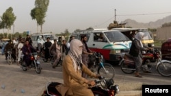Traffic is stopped as members of Afghan Special Forces regroup after heavy clashes with the Taliban, at a checkpoint in Kandahar province, Afghanistan, July 13, 2021.