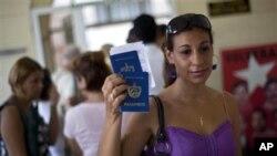 Một phụ nữ cho các nhà báo xem hộ chiếu của bà và con trai khi bà rời văn phòng di trú ở Havana Cuba