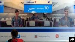 Seorang penumpang tengah memeriksa informasi di tempat penjualan tiket pesawat Malaysia Airways di Bandara Internasional Kuala Lumpur di Sepang, luar Kuala Lumpur (8/3).