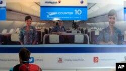 一名乘客正在吉隆坡国际机场马航公司问讯处查询失联航班信息
