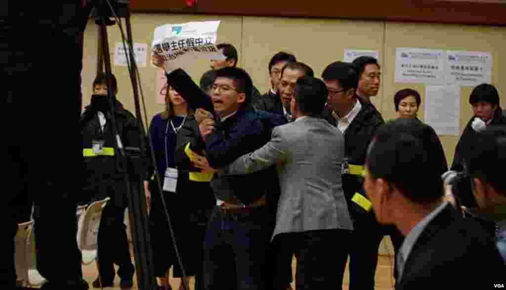 香港眾志秘書長黃之鋒在候選人簡介會場內示威被保安帶走。(香港眾志圖片)