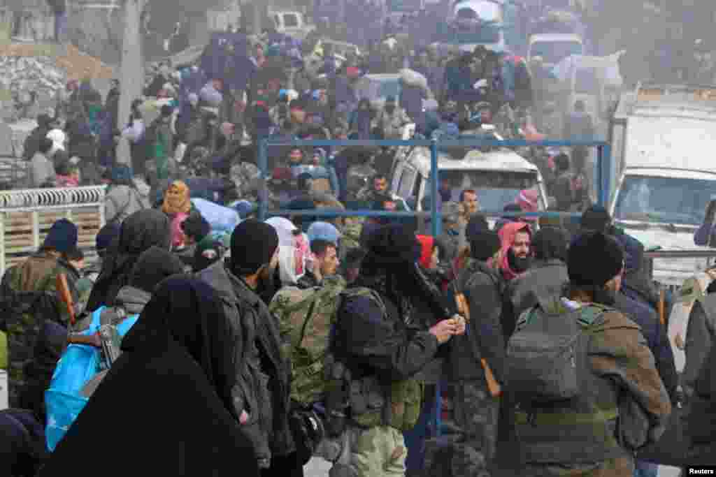 Rebel fighters and civilians gather as they wait to be evacuated from a rebel-held sector of eastern Aleppo, Syria, Dec. 16, 2016.