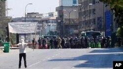 星期五一名反政府抗議者在敘利亞霍姆斯市附近面對防暴警察