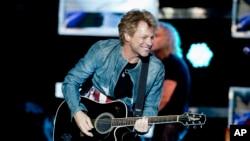 FILE - Singer Jon Bon Jovi play the guitar during a concert of the American rock band Bon Jovi in Madrid, Spain, Thursday June 27, 2013. (AP Photo/Abraham Caro Marin)