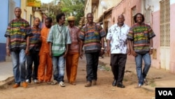The eight members of Super Mama Djombo, including founder Ze Manel Fortes and composer Atchutchi, walk through the streets of Bissau's old town, Guinea-Bissau, May 2, 2012. (K. Thomas/VOA)