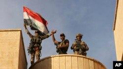 Fuerzas especiales iraquíes celebran con la bandera de Irak en alto por la recuperación de Bartella, en las afueras de Mosul.