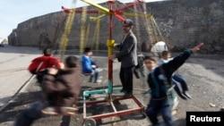 کودکان در ترکیه درحال بازی با یک چرخ فلک دست ساز . دیار بکر، دسامبر ۲۰۰۹