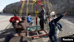 FILE - Turkish children are seen playing on a make-shift carousel.