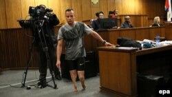 L'ancien champion paralympique Oscar Pistorius, au centre, marche sans ses prothèses dans la salle d'audience pendant la procédure, le troisième jour de son audience de détermination de la peine à la Haute Cour de Pretoria, Afrique du Sud, 15 juin 2016.