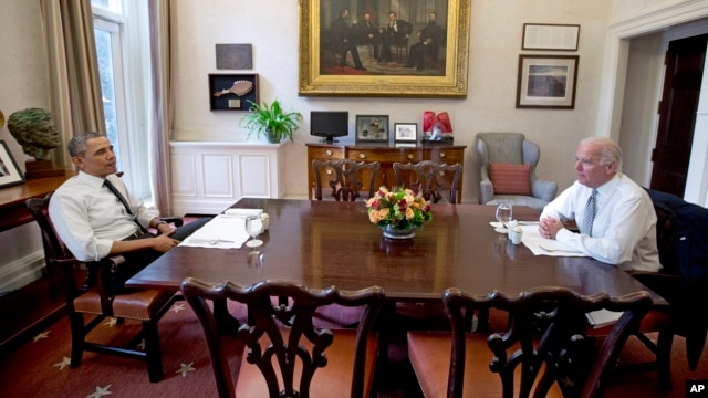 President Barack Obama and Vice President Joe Biden talk during a photo-op as they meet for lunch in the private dining room of the White House in Washington, Jan. 8, 2014.
