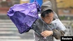 태풍 '레끼마' 상륙한 중국 산둥성 옌타이에서 여성이 우산으로 바람을 막고 있다.