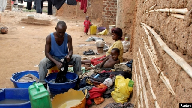 FILE - A Ugandan man cleans his clothes at the Makerere Kivulu slums in Kampala.