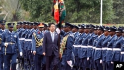 Japan's Prime Minister Shinzo Abe inspects a military honor guard in Nairobi, Kenya, where he's visiting as part of an international development conference, Aug. 26, 2016.