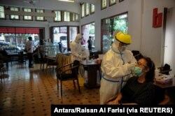 Petugas kesehatan mengambil sampel antigen cepat dari pengunjung di tengah pandemi COVID-19 di Bandung, Jawa Barat, 30 Desember 2020. (Foto: Antara/Raisan Al Farisi via REUTERS)