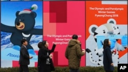 People pass by posters showing the 2018 Pyeongchang Winter Olympic mascots in Seoul, South Korea, Jan. 17, 2018.