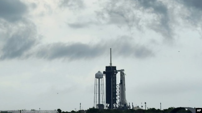 Clouds pass over the SpaceX Falcon 9, with the Crew Dragon spacecraft on top of the rocket, as it sits on Launch Pad 39-A Wednesday, May 27, 2020, at Kennedy Space Center in Cape Canaveral, Fla. (AP Photo/David J. Phillip)