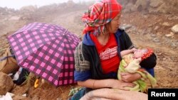 FILE - A woman holds her child as she waits while rescuers search for her husband, a victim of a landslide in Vietnam's northern province of Yen Bai on September 8, 2012.