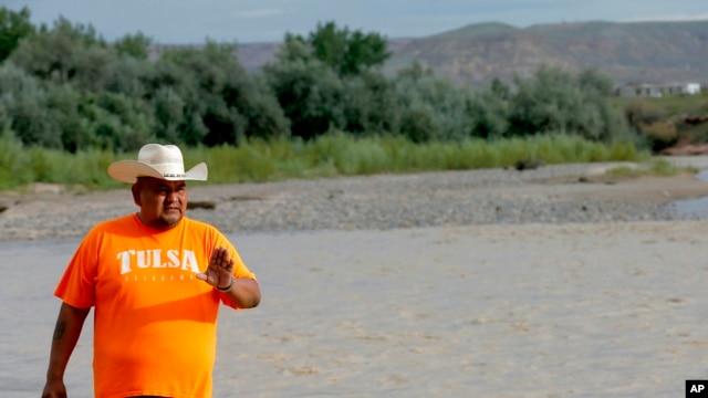 FILE - Navajo Nation Council Delegate Davis Filfred walks along the San Juan River, Aug. 11, 2015, in Montezuma Creek, Utah.