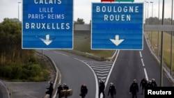 Des policiers anti-émeutes ayant repoussé des migrants qui bloquaient la route à Coquelles près de Calais, en France, le 2 août 2015 (REUTERS/Pascal Rossignol)