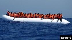 Des migrants arrivent près de la côte Libyenne abord d'un canoe gonflable, 3 aout 2015.