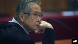 FILE - Former President Alberto Fujimori, photographed through a glass window, attending his trial at a police base on the outskirts of Lima, Peru, June 28, 2016.