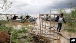 一名柬埔寨人7月27日从他停泊在金边郊外湄公河上的渔船走上岸