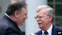 Secretary of State Mike Pompeo, left, and national security adviser John Bolton, right, talk before the start of a news conference in the Rose Garden of the White House in Washington, June 7, 2018.