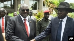 FILE - South Sudan's First Vice President Riek Machar, left, and President Salva Kiir, right, shake hands following the first meeting of a new transitional coalition government, in the capital Juba, April 29, 2016.